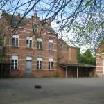 Speelplaats met links klooster en rechts één van de twee centraal gelegen klaslokalen